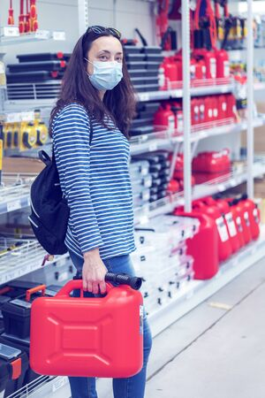 Woman in protective mask in a store with a canister. pandemic concept. Pandemic Shopping. vertical photo. toned.