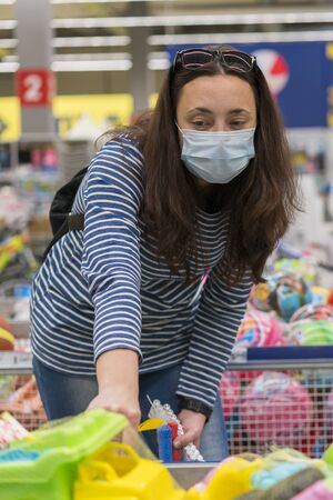 Woman in a protective mask in a supermarket chooses children's toys. toned. vertical photo.