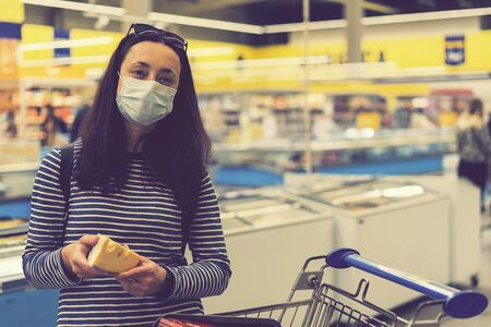 woman in protective medical mask in a supermarket chooses cheese. pandemic and covid-19 concept. Hand of the buyer with a piece of cheese in the store. toned.