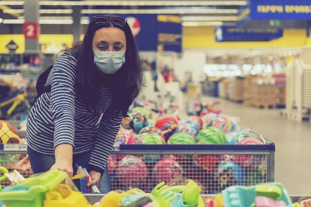 Woman in a protective mask in a supermarket chooses children's toys. toned.
