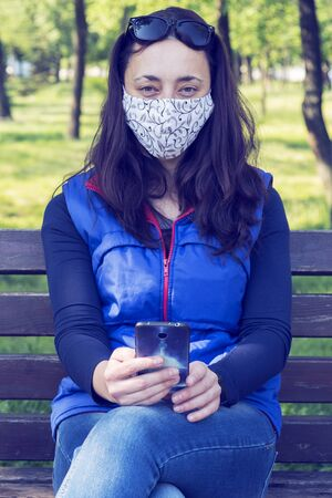 Portrait of brunette woman in a protective mask sitting on a bench in the park, sunny spring day. oronavirus concept. respiratory protection. vertical photo. toned. 免版税图像 - 148957273