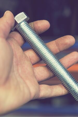 hand holds an iron bolt. repair concept. close-up. vertical photo. 免版税图像 - 149160055