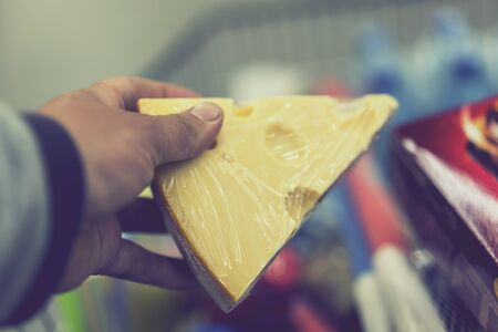 Male hand holds cheese in a supermarket. toned.