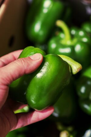 A man chooses green bell peppers in a grocery store, at the market. Hand take the pepper from a vegetable basket. Man's hand is holding Red Bell pepper from supermarket shelf. close-up. vertical photo.