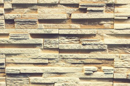 Stacked stone wall, natural stone cladding. Stone wall for background,Slab stone wall texture. Wall background of volcanic andesite basalt stone texture. toned. 免版税图像