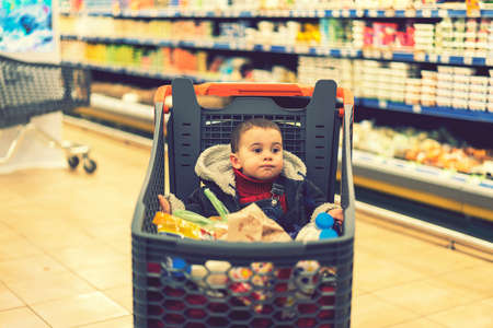 Full cart with food in the supermarket. In the cart sits a baby. toned
