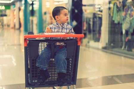 Baby boy rides in a trolley through a shopping center. toned
