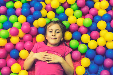 Cute and pretty little girl looking at camera inside heap of multi-colored balloons. toned