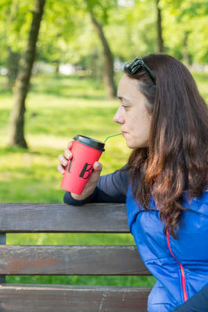 Beautiful Caucasian woman with long brown hair sitting on a yoga mat in the park drinking a cup of tea or coffee and smiling. Middle-aged athletic woman with long hair drinks coffee in a park. toned