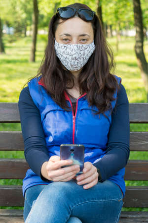 Portrait of brunette woman in a protective mask sitting on a bench in the park, sunny spring day. oronavirus concept. respiratory protection. vertical photo