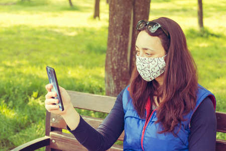 The woman sitting on the bench in the park and wearing a protective mask and using smartphone . Coronavirus concept. toned