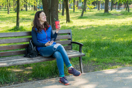 Beautiful Caucasian woman with long brown hair sitting in the park wearing a protective mask drinking a cup of tea or coffee and smiling. toned 免版税图像