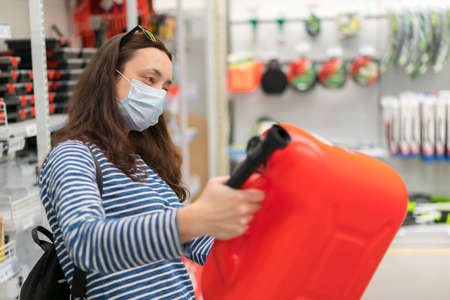 Woman in protective mask in a store with a canister. pandemic concept. Pandemic Shopping 免版税图像