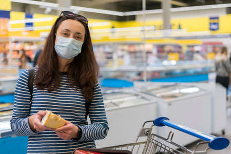 woman in protective medical mask in a supermarket chooses cheese. pandemic and covid-19 concept. Hand of the buyer with a piece of cheese in the store 免版税图像