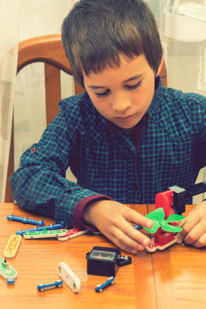 The boy playing an electric constructor. The child is played by intellectual toys. A boy in a blue shirt masters electronics. The concept of early development of children. vertical photo. toned