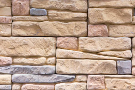 Stacked stone wall, natural stone cladding. Stone wall for background,Slab stone wall texture. Wall background of volcanic andesite basalt stone texture.