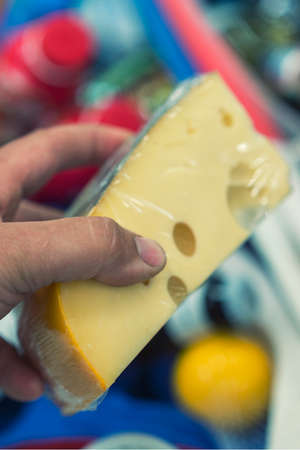 Male hand holds cheese in a supermarket. vertical photo toned 免版税图像