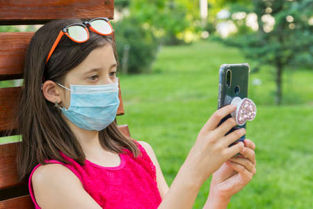 girl in protective mask holding a smartphone. teen girl siting on bench in green park with mobile phone. First stage of loosening coronavirus restrictions and self-isolation