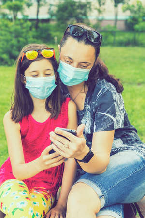 Mom with daughter in the park in medical masks. Family of mom and kid wearing protective medical mask for prevent virus outdoors in the park. new normal concept. toned