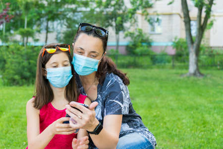 Mom with daughter in the park in medical masks. Family of mom and kid wearing protective medical mask for prevent virus outdoors in the park. new normal concept. copy space 免版税图像