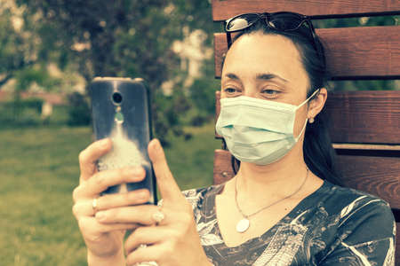 Young woman in protective mask holding a smartphone. Woman siting on bench in green park with mobile phone. First stage of loosening coronavirus restrictions and self-isolation. toned