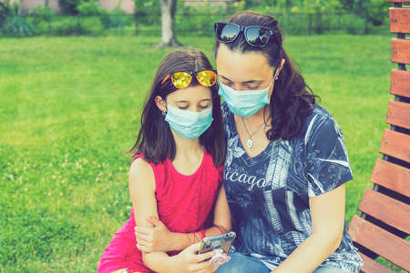 Mom with daughter in the park in medical masks. Family of mom and kid wearing protective medical mask for prevent virus outdoors in the park. new normal concept 免版税图像 - 151126288
