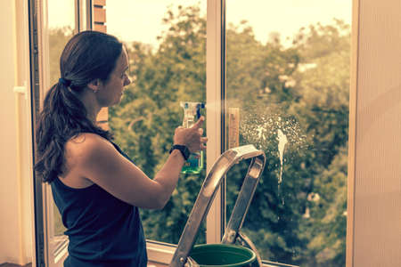 Back view of the young woman who washing the window with rag and window cleaner in the room. Cute girl with long hair washes a glass with detergent. toned. selected focus 免版税图像 - 150884204