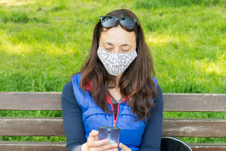 The woman sitting on the bench in the park and wearing a protective mask and using smartphone