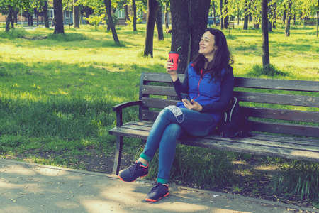 Beautiful Caucasian woman with long brown hair sitting on a yoga mat in the park drinking a cup of tea or coffee and smiling. Middle-aged athletic woman with long hair drinks coffee in a park. toned 免版税图像 - 164347137