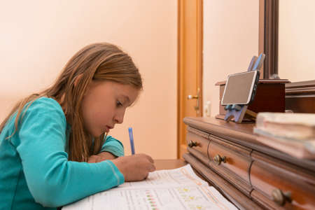 Home schooling. schoolgirl studying homework math during her online lesson at home, social distance during quarantine, self-isolation, online education concept, home schooler. toned 免版税图像