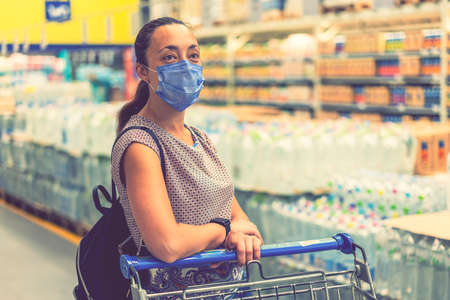 Alarmed female wears medical mask against virus while shopping in supermarket or store- health, safety and pandemic concept. Girl shopaholic in mall. toned 免版税图像 - 164347140