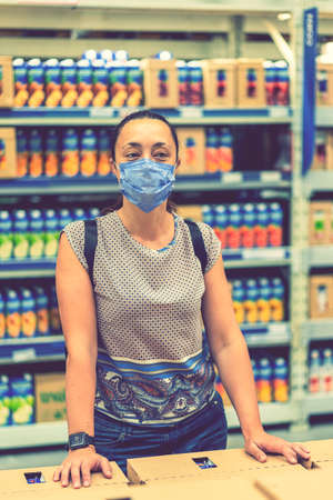 Alarmed female wears medical mask against virus while grocery shopping in supermarket or store- health, safety and pandemic concept. vertical photo. toned 免版税图像