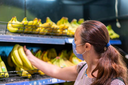 Focused woman in face mask choosing fruits, taking bananas from shelves in grocery store. Customer in supermarket. Side view. Shopping during epidemic concept 免版税图像