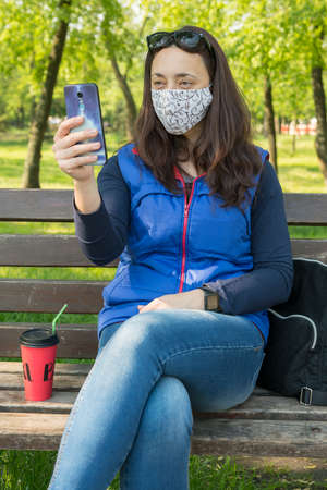 Portrait of brunette woman in a protective mask sitting on a bench in the park, sunny spring day. oronavirus concept. respiratory protection. vertical photo. toned 免版税图像