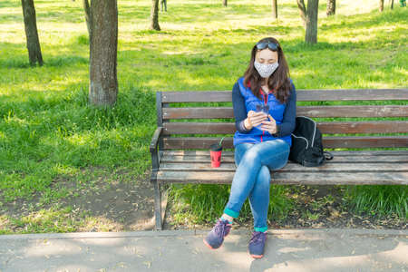 The woman sitting on the bench in the park and wearing a protective mask and using smartphone . 免版税图像