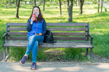 Beautiful Caucasian woman with long brown hair sitting on a yoga mat in the park drinking a cup of tea or coffee and smiling. Middle-aged athletic woman with long hair drinks coffee in a park 免版税图像