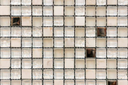 Ceramic mosaic tiles with white and brown embossed squares to decorate the kitchen, bathroom or pool. Mosaic of brown marble in the form of squares 免版税图像