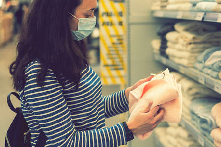 Woman in medical mask choosing goods in a store. Concept of shopping during quarantine pandemic. shopping at the time of the pandemic. Beautiful young women in a flu mask. toned
