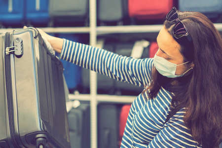 A young woman in a disposable mask choosing a suitcase for the upcoming vacation after the end of the  pandemic. Shopping at supermarket during epidemic. toned