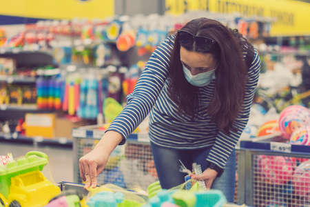 Woman in a protective mask in a supermarket chooses childrens toys. toned