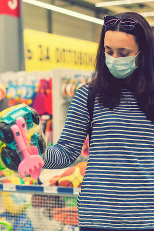 Woman in a protective mask in a supermarket chooses childrens toys. toned. vertical photo. toned