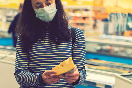 woman in protective medical mask in a supermarket chooses cheese. pandemic concept. Hand of the buyer with a piece of cheese in the store. toned 免版税图像