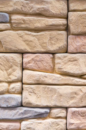 Stacked stone wall, natural stone cladding. Stone wall for background,Slab stone wall texture. Wall background of volcanic andesite basalt stone texture. vertical photo