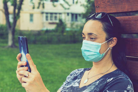 Portrait of a Girl with medical mask at park with smartphone during quarantine. A young girl in a medical mask sits on bench in the park and use smartphone. toned