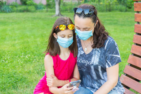 Mom with daughter in the park in medical masks. Family of mom and kid wearing protective medical mask for prevent virus outdoors in the park. new normal concept. copy space. toned. copy space
