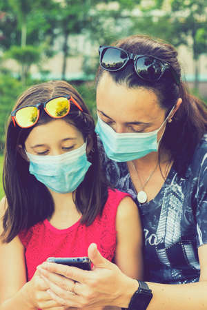 Mom with daughter in the park in medical masks. Family of mom and kid wearing protective medical mask for prevent virus outdoors in the park. new normal concept. vertical photo. toned
