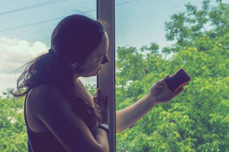 Back view of the young woman who washing the window with rag and window cleaner in the room. Cute girl with long hair washes a glass with detergent. toned. selected focus. toned 免版税图像