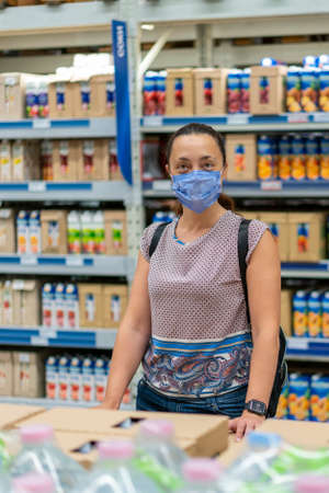 Alarmed female wears medical mask against coronavirus while grocery shopping in supermarket or store- health, safety and pandemic concept. vertical photo. toned