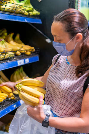Focused woman in face mask choosing fruits, taking bananas from shelves in grocery store. Customer in supermarket. Side view. Shopping during epidemic concept. toned. vertical photo