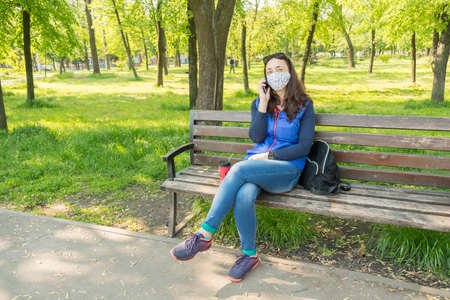 The woman sitting on the bench in the park and wearing a protective mask and using smartphone . Coronavirus concept. toned 免版税图像 - 152957628